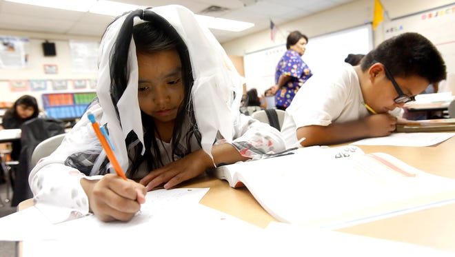 Lanaya Clark, left, and Maysah Nolan do classwork Oct. 30, 2015, at Mesa Elementary School in Shiprock, part of the Central Consolidated School District. Students throughout the district will receive free school supplies this year.