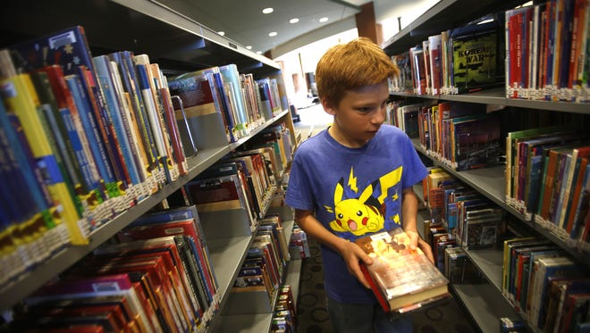 Noah Mirabal searches for books May 24, 2016, at the Farmington Public Library. The library will be closed Thursday through Sunday for Thanksgiving.