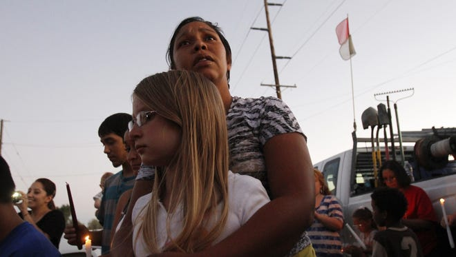In this file photo, Dana Davila, holds her niece Guinie Wade, as she speaks about her father, John J. Rogers, Thursday, Aug. 28, 2014, during a candlelight vigil at her family's home in Bloomfield.