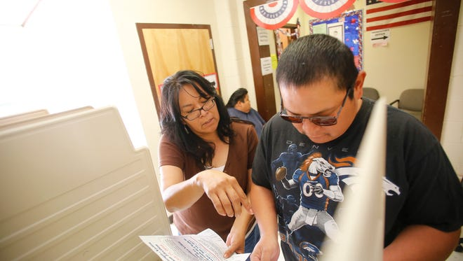 Alberta King, office administrator with the Navajo Election Administration, explains the ballot to voter Philo Pinto, Friday, July 17, 2015, at the Navajo Election Administration - Northern Agency Office in Shiprock, N.M.