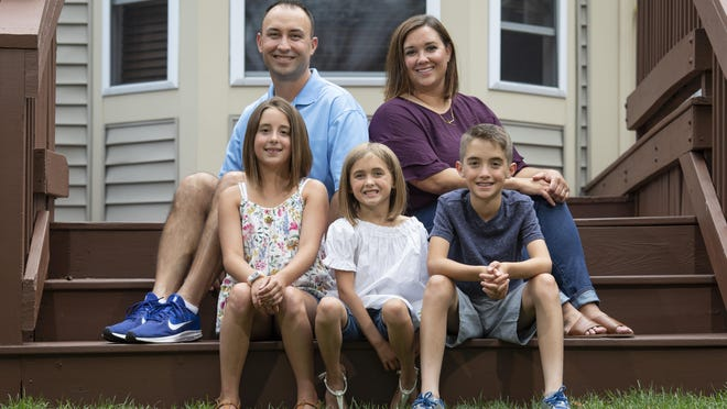 Kara Schooley, 39, and her husband Kurt Schooley, 42, along with their kids, from left,  Amelia, 10, Parker, 6, and Bennett, 10, sit outside their house in Hilliard. Amelia and Bennett are twins.
