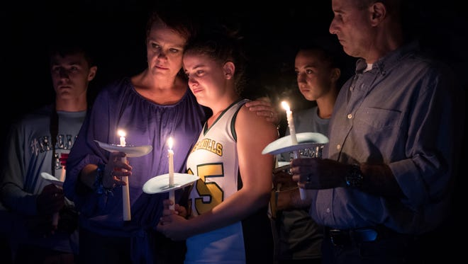 Mallory Grossman's mother, Dianne, hugs her daughter Carlee during Thursday night's candlelight vigil at White Meadow Lake Country Club in Rockaway Township. Mallory's father, Seth, is at right.