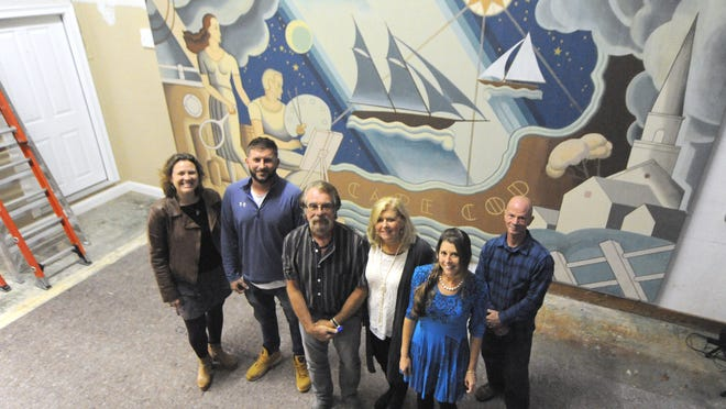 A team of restorers and conservators has restored two large murals that once hung in a Hyannis theater. Cape Cod Picture Framing & Restoration owner and mural project manager Ron Lindholm, third from left, was joined by his wife, Terry Lindholm, third from right; daughter, restorer Tracy Nee, second from right; son, conservator Peter Lindholm, second from left; restorer Shannon Davis, left; and  conservator Lance Walker, right.