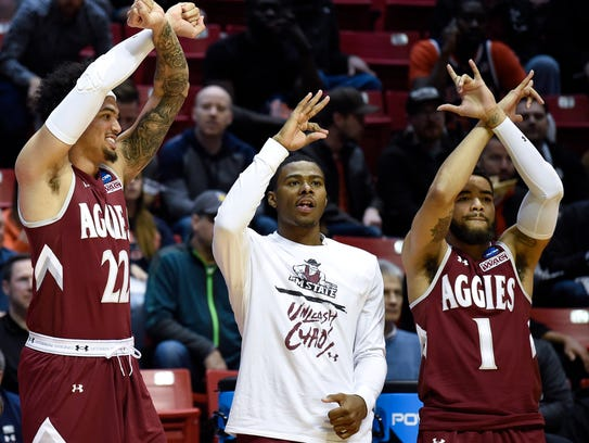 New Mexico State players react on the bench during