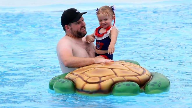 Matt Garner helps his daughter, Hadlee, 2, onto the floating turtle in the activity pool, Saturday, July 4, 2020, at Parrot Island Waterpark.