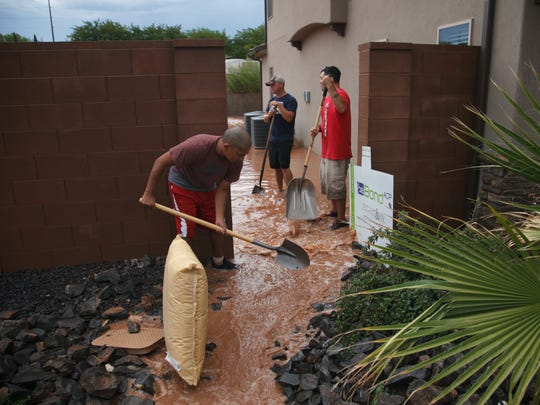 Washington City residents help clean up the mess left behind after flood waters rushed down the center of town Monday, Aug. 18, 2014.