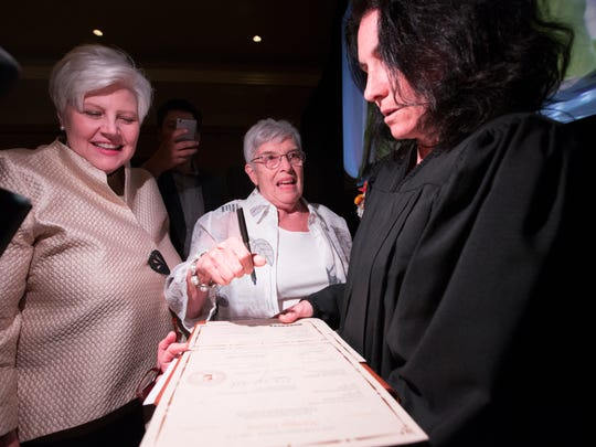 Katharine Halpin (left) and Bonnie Meyer sign their wedding license after being married by City of Phoenix Judge Marianne Bayardi .