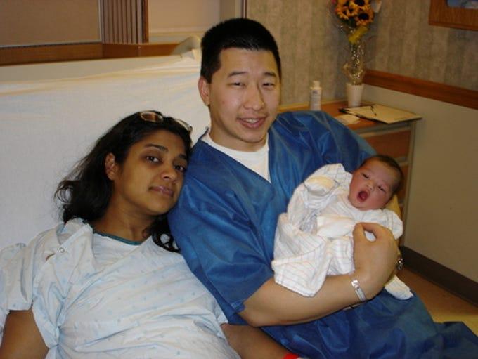 Pratima Sampat-Mar and John Mar holding their daughter,
