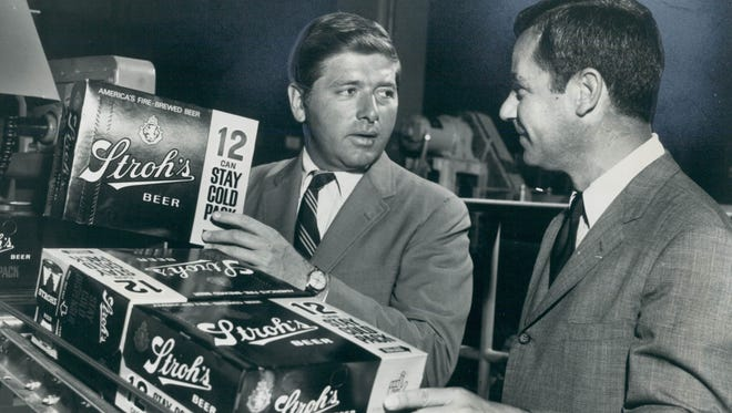 JOHN W. STROH Jr. (left), director of packaging for Stroh Brewery Co., inspects his company's new stay coldpack aluminium-foil carton for keeping beverages cold up to six hoursafter refrigeration.