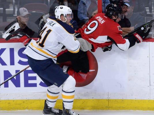 Buffalo Sabres' Justin Falk, left, hits Ottawa Senators' Bobby Ryan into the boards during first-period preseason NHL hockey game action in Ottawa, Ontario, Friday, Oct. 7, 2016. (Sean Kilpatrick/The Canadian Press via AP)