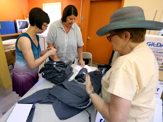 Stephanie Patterson, events coordinator for the Salem Art Association, center, sorts t-shirts with Victoria Edwards, left, and Kathie Stevens during a Salem Art Fair committee meeting at the Bush Barn Art Center.