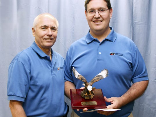 """Account supervisor Jason Seibert, right, receives the Master """"Eagle"""" recently from Michael Evanish, manager of Pennsylvania Farm Bureau's MSC Business Services."""