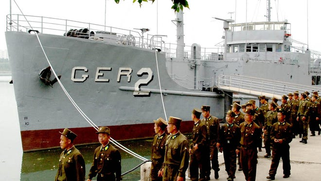 North Korean soldiers pass by the USS Pueblo at its dock in Pyongyang in June 2006. The ship, seized by North Korea in 1968, is North Korea's greatest Cold War prize.