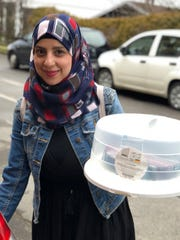 Reem Helani holds one of her homemade cakes for sale