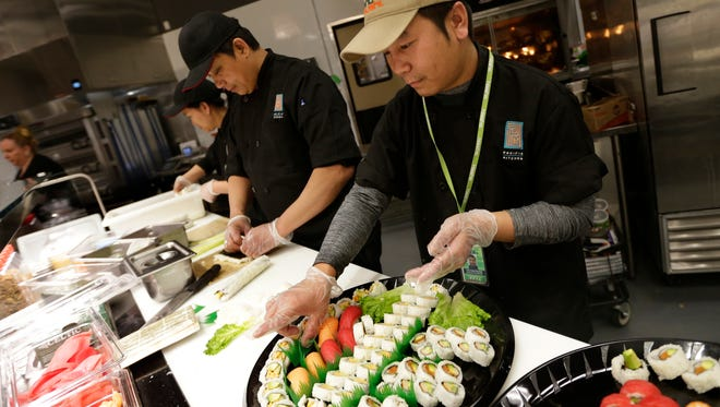 Van Cung Thawng (right), regional coordinator with Hissho Sushi, makes sushi rolls with sushi chefs including Aung Zar Shar (center).