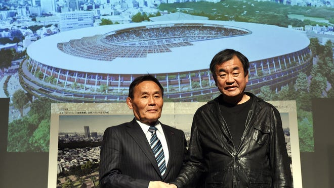 Japan Sports Council President Kazumi Ohigashi, left, shakes hands with architect Kengo Kuma during a Dec. 22, 2015, news conference announcing a new design for the 2020 Tokyo Olympics stadium.