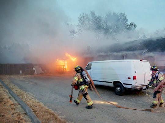 Bremerton firefighters carry a hose line to battle a duplex fire on Hemlock Street in East Bremerton Friday evening.