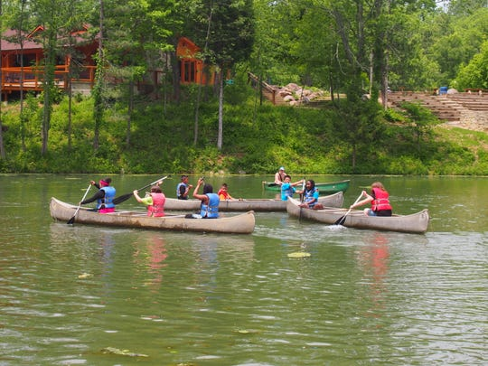 "Canoeing is one of many activities fourth-graders try at Flat Rock YMCA Camp. ""For most of these kids, it's the first time they've been out of their neighborhood,"" teacher Julie Beaty said."