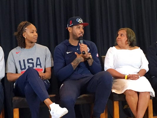 New York Knicks forward Carmelo Anthony, center, with Tanika Catchings of the WNBA Indiana Fever, left, with Charisse Bremond Weaver, president and chief executive officer of Brotherhood Crusade, speaks as he spent the U.S. Olympic basketball team's precious day off running a two-hour town hall meeting at a South Los Angeles youth center Monday, July 25, 2016. Anthony gathered basketball stars, community leaders and police officers to speak with teenagers and young adults about the importance of respect, communication and safety. (AP Photo/Greg Beacham)