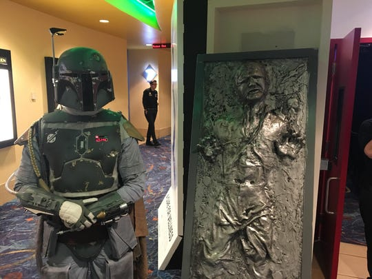 Boba Fett shows off his Han Solo trophy Thursday night at the Tulare Galaxy Theatre.