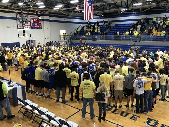 Players and spectators from White House and White House Heritage gather on the court to pray for White House High School student Mary Keith, who lost her battle with cancer.