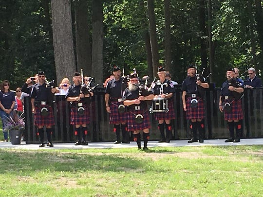 "Bagpipers pay tribute to military dog Cena with the playing of ""Amazing Grace."""