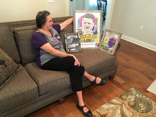 """In this Aug. 22, 2017 photo, Cornelia """"Coco"""" Orgeron, shows off memorabilia marking the ascension of her son, Ed Orgeron, to head coach at LSU, at her home in Larose, La. Ed Orgeron grew up an LSU fan in Cajun country along the Bayou Lafourche in Larose, Louisiana, where his mother still lives. The Tigers' coach is about to begin his first full season on the job after taking over for Les Miles during last season. His Louisiana and Cajun roots made him a popular choice to keep the job long term. (AP Photo/Brett Martel)"""