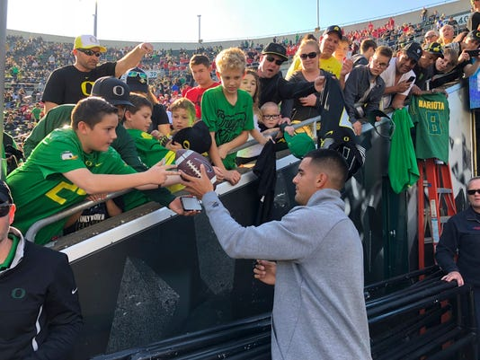 Former Oregon quarterback Marcus Mariota, now with the NFL Tennessee Titans, signs autographs for fans before the start of the Oregon Utah NCAA college football game Saturday, Oct. 28, 2017, in Eugene, Ore. (AP Photo/Chris Pietsch)