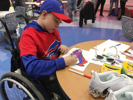 "Ian Cameron, a pediatric cancer patient at Buffalo's John R. Oishei Children's Hospital, joined Buffalo Bills players on Tuesday, Nov. 14, 2017, to customize cleats, which players will wear during their home game against the New England Patriots on Dec. 3. The event was held as part of the NFL's ""My Cause, My Cleats"" campaign in which players are allowed to wear their own style of footwear reflecting their commitment to charitable causes. (Photo by John Wawrow)"