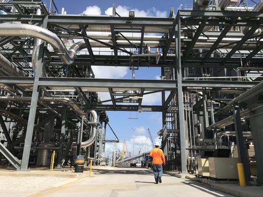 A worker walks on site at Florida Power & Light's Riviera Beach gas-fired power plant. Critics say the utility and the state now rely too much on natural gas, which also contributes to global warming.