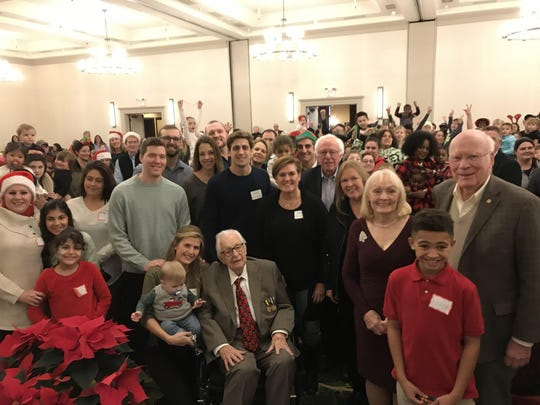 Burlington philanthropist and businessman Tony Pomerleau, seated, poses with friends and family members at the 38th annual Pomerleau Family Holiday Party at the Burlington Hilton. Pomerleau sponsored the party for community families in need. His family announced his death Friday morning.