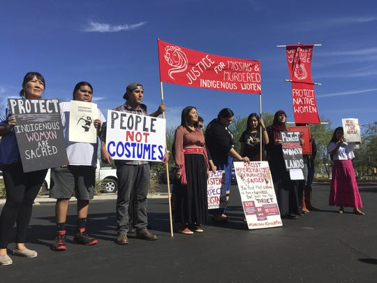 "Native American protesters stand outside the Phoenix office of Yandy.com, a retailer of ""sexy Native American"" costumes on Wednesday, Oct. 24, 2018. For some ethnic and racial groups, Halloween has long been haunted by costumes that perpetuate stereotypes and instances of cultural appropriation."