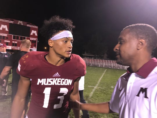 Muskegon quarterback Cameron Martinez talks to Athletic Director/basketball coach Keith Guy after victory over Detroit King  Martinez