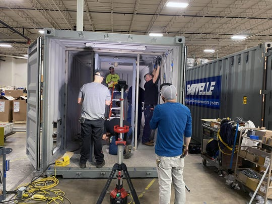 Workers at Battelle's West Jefferson, Ohio facility build one of its Critical Care Decontamination Systems, which Battelle says can sterilize 80,000 masks per day.
