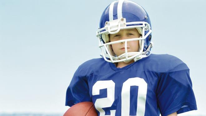 portrait of a boy wearing a helmet holding a football