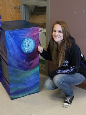 Bloomfield High School's Serenity Gundlach poses with a Little Free Library, which has been placed at the Nageezi Chapter House. She, along with Tyler Brown, Nathan Gutierrez and Brandon Gutierrez, painted the bin in an outer space theme.