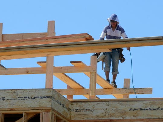 A worker of RW Fisher Contruction, LLC of Toms River covers his head with a hood to beat the heat while building a home on Brooklyn Avenue in Sea Girt, NJ Friday July 15, 2016.
