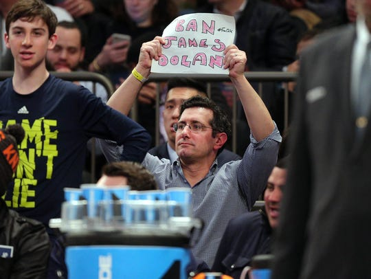 A fan holds a sign directed at New York Knicks owner