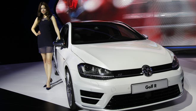 A model poses next to a Volkswagen Golf R at the Seoul Motor Show