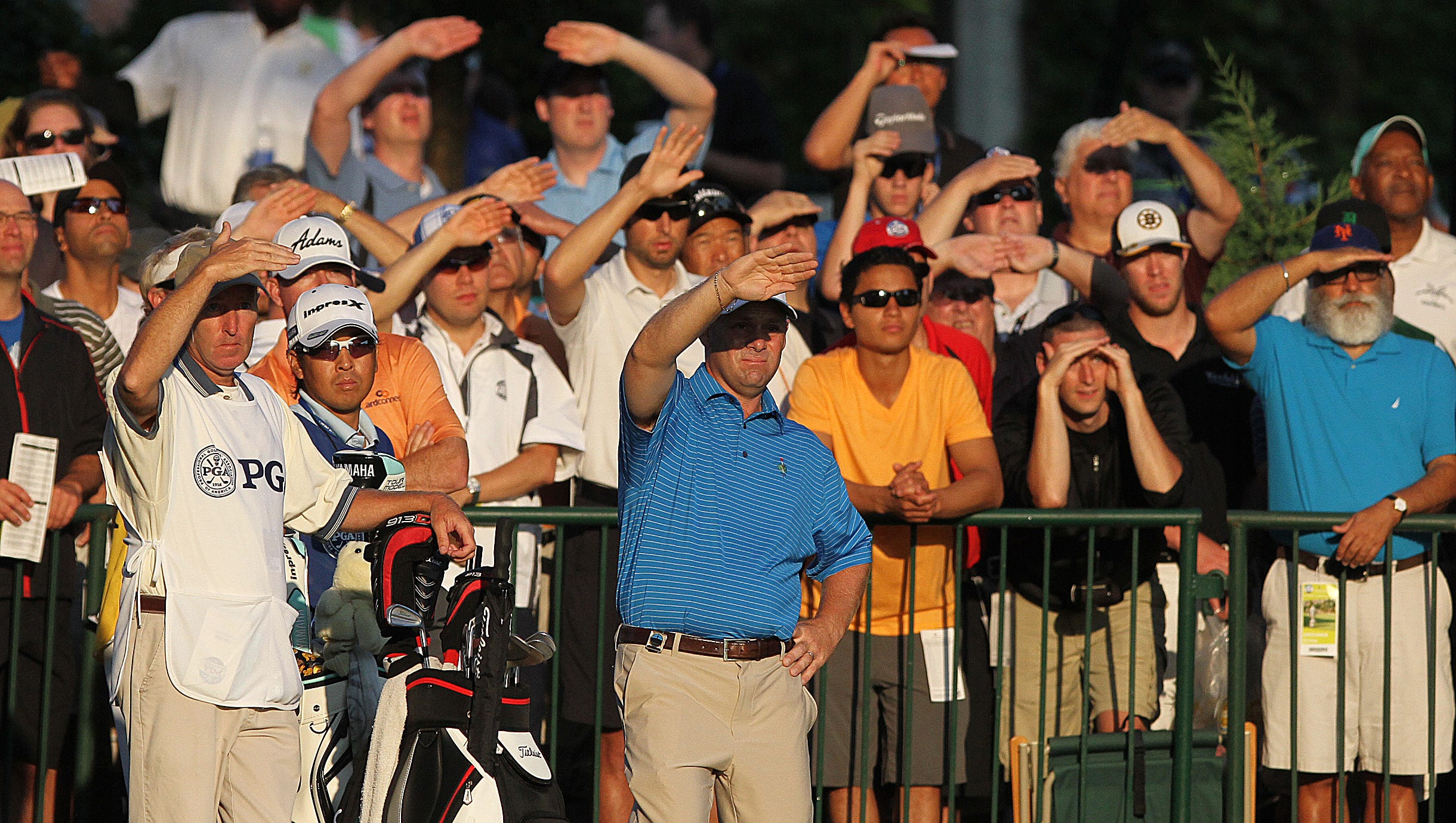 Golfers and spectators sheild their eyes from the early morning sun Thursday,