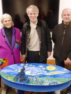 Malden Sketch Group members Cambia Davis, John Preotle and Fred Seager pose in front of a hand-painted table. The group is celebrating its 25th anniversary.