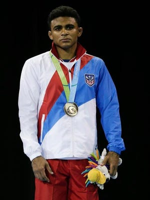 """Pureto Rico's Franklin Gomez poses wearing his bronze medal won in the 2015 Pan Am Games. Gomez waited patiently for two weeks. """"Waiting can be anxious, but I am not in control of the day I wrestle,"""" he said."""