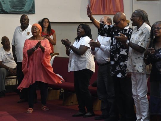 Church attendees sing during a prayer vigil in honor