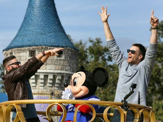 Super Bowl MVP Julian Edelman and Patriots quarterback Tom Brady, right, celebrate with Mickey Mouse in the Super Bowl victory parade in the Magic Kingdom, at Walt Disney World, in Lake Buena Vista, Fla., Monday, Feb. 4, 2019. (Joe Burbank/Orlando Sentinel via AP)