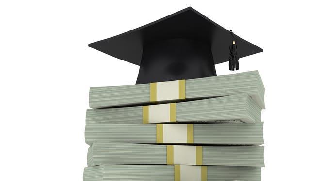 Graduation cap on stacks of money