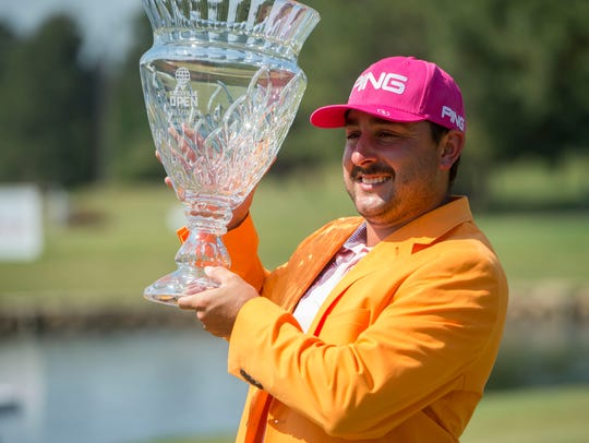 Stephan Jaeger carries the trophy and wears the orange jacket after winning the Knoxville Open on Sunday.