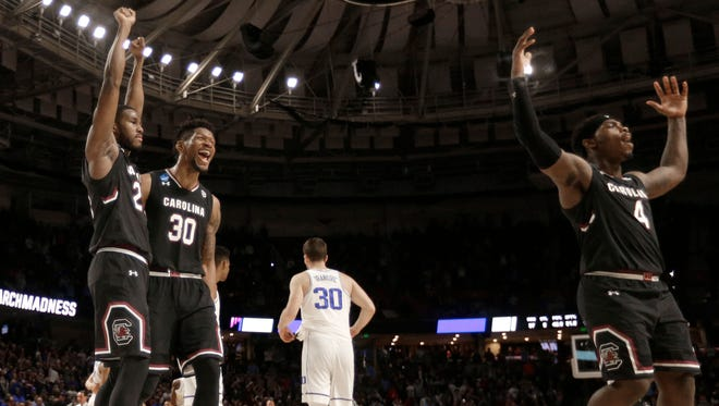 South Carolina's Rakym Felder (4), Chris Silva (30) and Justin McKie (20) celebrates as Duke's Antonio Vrankovic (30) walks off the court after a second-round game of the NCAA men's college basketball tournament in Greenville, S.C., Sunday, March 19, 2017. (AP Photo/Rainier Ehrhardt)
