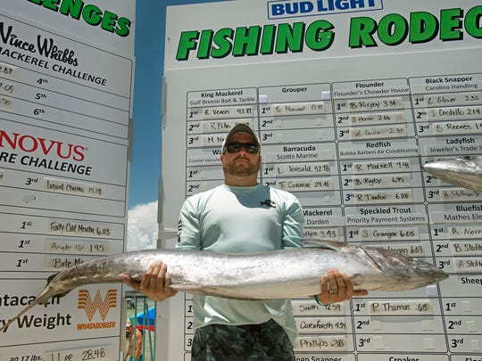 Matt Richey shows off his 49.53 pound king mackerel Sunday, June 24, 2018 during the Bud Light Fishing Rodeo at Flounders at Quietwater Beach.
