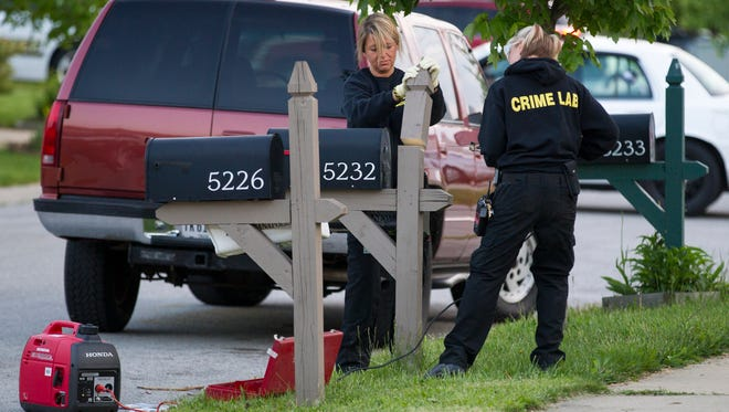 Crime lab workers remove part of a mail box post during their investigation of the scene of an overnight shooting that killed two and wounded three others on the 6000 block of Lakeside Manor Avenue, Indianapolis, Tuesday, May 20, 2014.