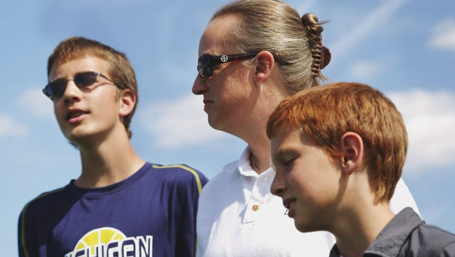 Kris Bieniewicz of Westland, Mich., seen with her sons Josh Bieniewicz, 9, and Kyle Bieniewicz, 14, says of the incident that led to her husband John's death: 'We're not going to let the evilness that took place beat us. ... We're going to persevere through it.'